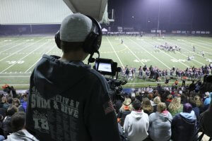 A student operates the camera at a football game.