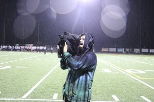 BGHS Junior Benjamin Cahoon operates a camera at a football game