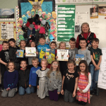 Lyla Smith's first grade class posing with the books they sent to Paradise, California
