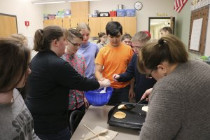 Kids in the peer mentoring program line up to get pancakes after making the batter