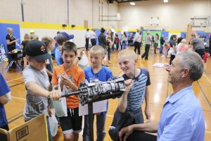 Fourth graders attempt to crank an engine at the automotive careers booth