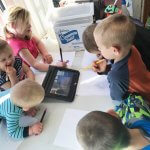 6 siblings all looking at an iPad looking at a remote learning lesson