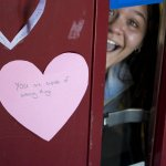 Student peeks out from door with paper heart on it